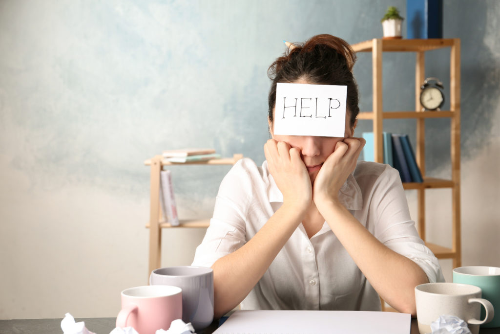 Young woman with note HELP on forehead at workplace. Space for text